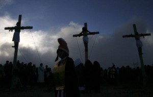 Three men depicting Jesus Christ and two thieves are fastened to wooden cross during Holy Week celebrations in La Paz
